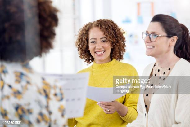 businesswomen having informal meeting in office - business strategy stock pictures, royalty-free photos & images