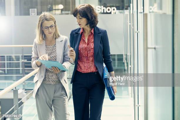 businesswomen having meeting in corridor of office - position stock-fotos und bilder