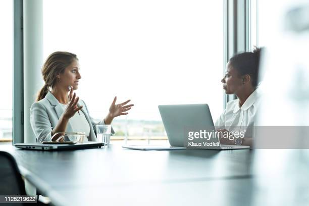 businesswomen having meeting with laptops in boardroom - manager stock pictures, royalty-free photos & images