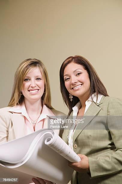 Businesswomen holding blueprints