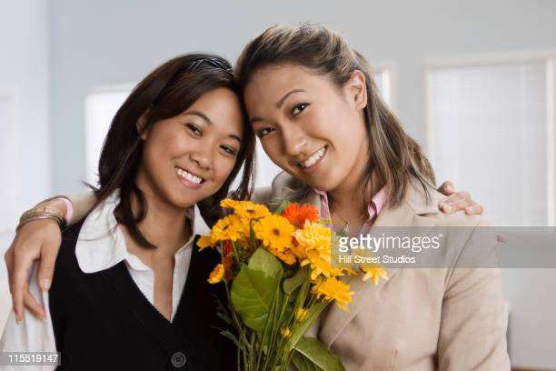 businesswomen holding flowers and hugging - gardena california stock pictures, royalty-free photos & images