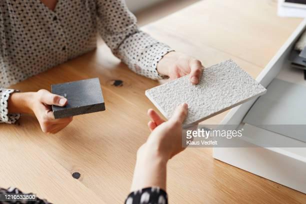 businesswomen holding samples over table in office - gestalterischer beruf stock-fotos und bilder
