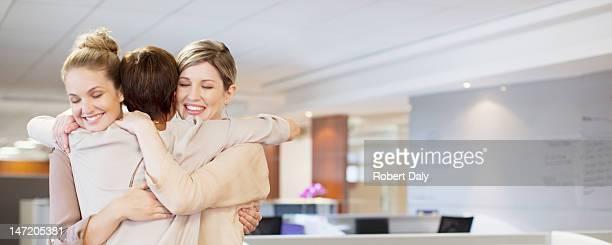 Businesswomen hugging in office