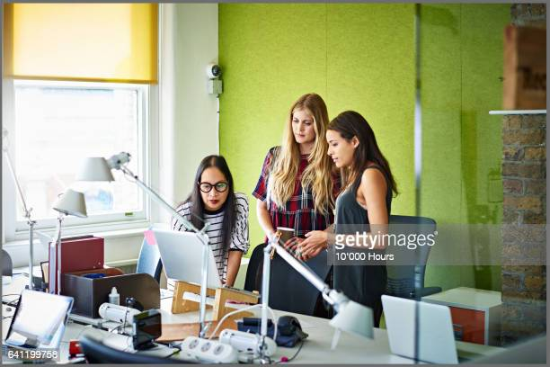 Businesswomen in a start-up office evaluating information on a laptop