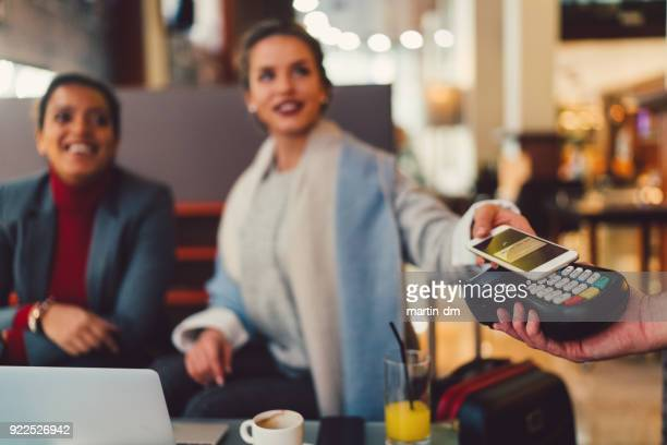 businesswomen in cafe paying contactless with digital wallet - nfc stock pictures, royalty-free photos & images