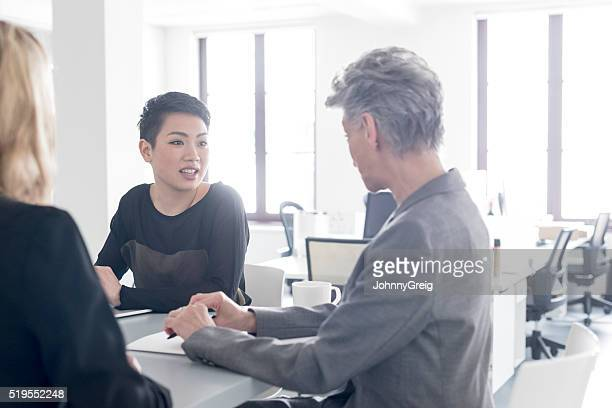 Businesswomen in meeting, young woman with short black hair talking