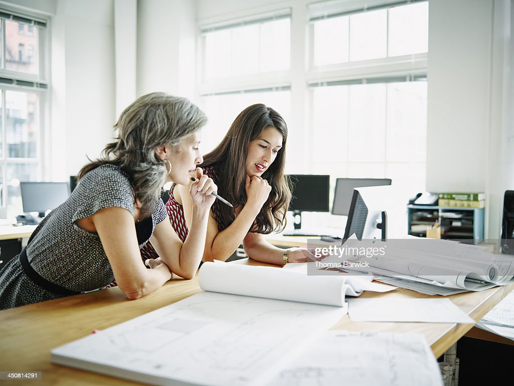 Businesswomen leaning on table discussing plans : Stock Photo