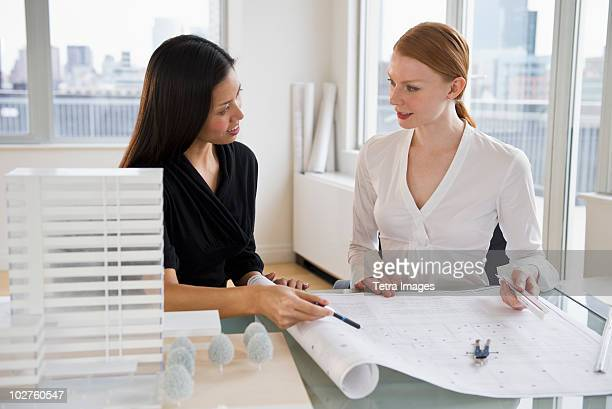 Businesswomen looking at blueprints