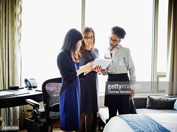 Businesswomen looking at digital tablet in hotel