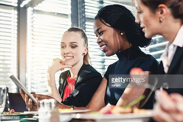 Businesswomen Looking at Smart Phone and Laughing During Business Lunch