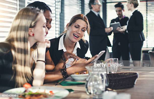 Businesswomen Looking at Smart Phone During Business Lunch and Laughing