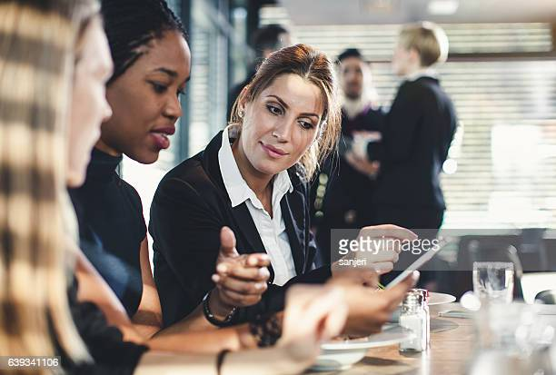 Businesswomen Looking at Smart Phone During Business Lunch