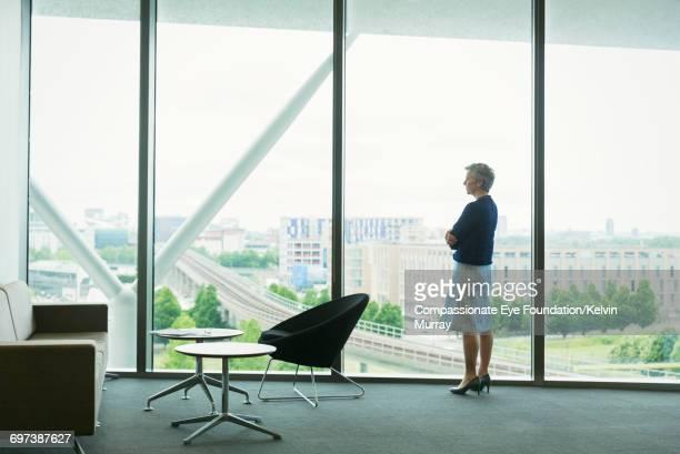 Businesswomen looking out window in office