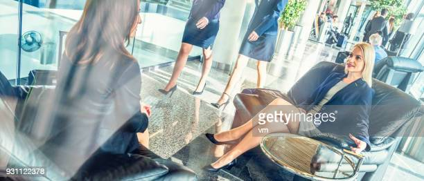 businesswomen lounging at an airport - cross legged stock pictures, royalty-free photos & images