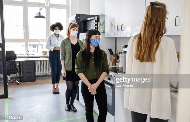 businesswomen maintaining social distancing in office cafeteria - distant stock pictures, royalty-free photos & images
