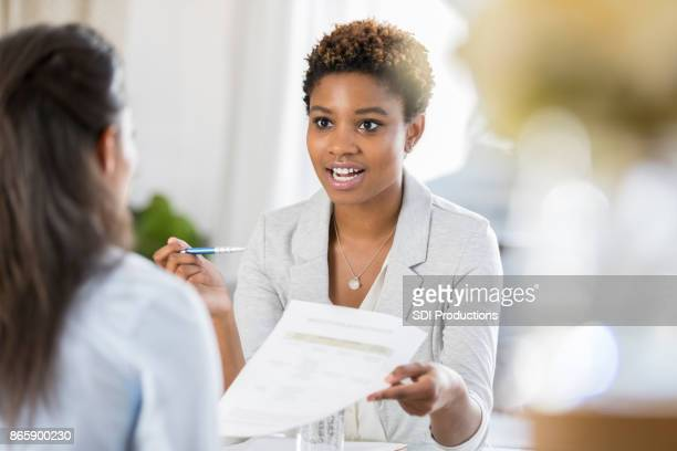 businesswomen meet to discuss document - counseling stock pictures, royalty-free photos & images