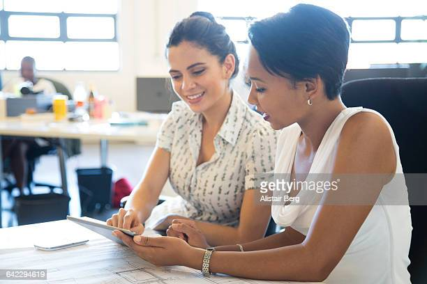 businesswomen meeting in an open plan office - vanguardians stock pictures, royalty-free photos & images