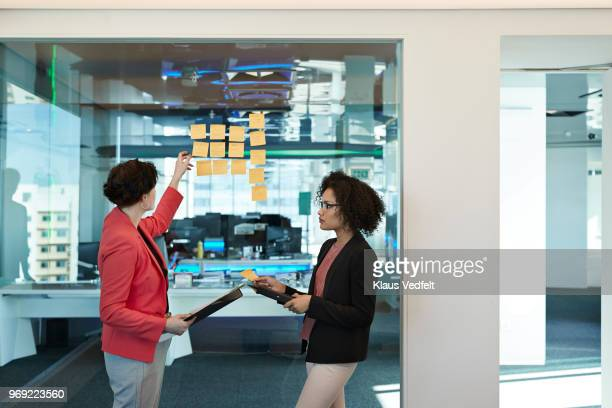 businesswomen putting notes on glass wall inside corner office - gray blazer stock pictures, royalty-free photos & images