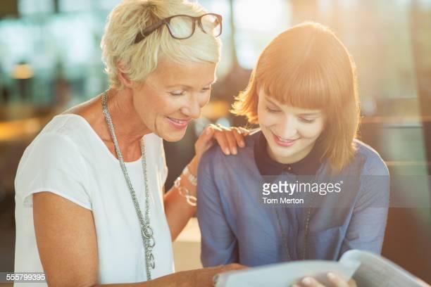 Businesswomen reading paperwork in office