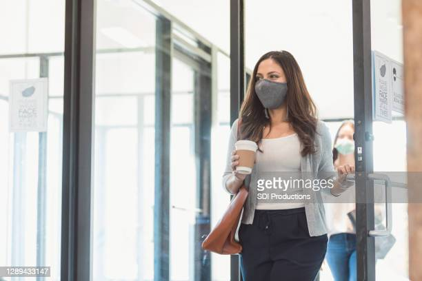 businesswomen return to office during covid-19 pandemic - arrival stock pictures, royalty-free photos & images