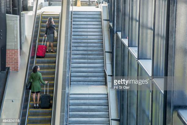 Businesswomen riding escalator