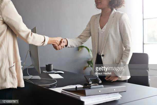 businesswomen shaking hands at modern workplace - cream coloured blazer stock pictures, royalty-free photos & images