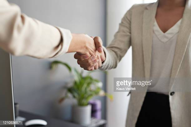 businesswomen shaking hands at workplace - cream coloured blazer stock pictures, royalty-free photos & images
