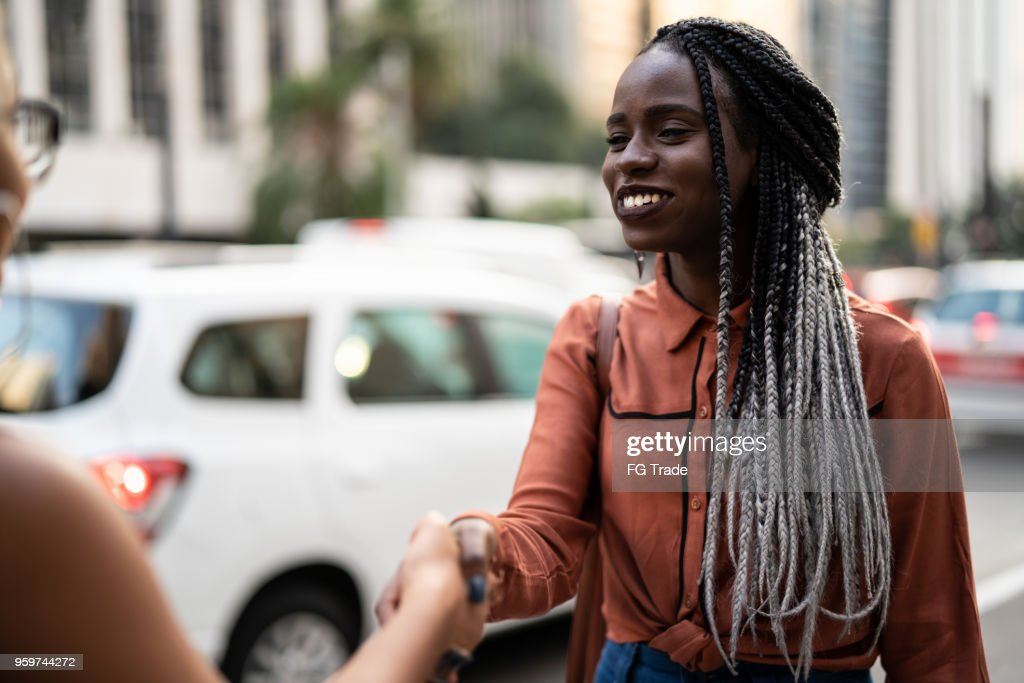 Businesswomen shaking hands in meeting at city : Stock Photo