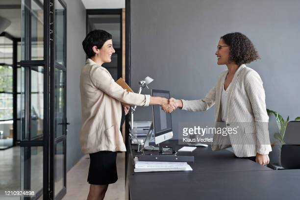 businesswomen shaking hands in modern office - cream coloured blazer stock pictures, royalty-free photos & images