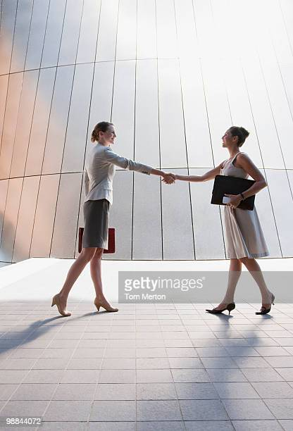 Businesswomen shaking hands outdoors