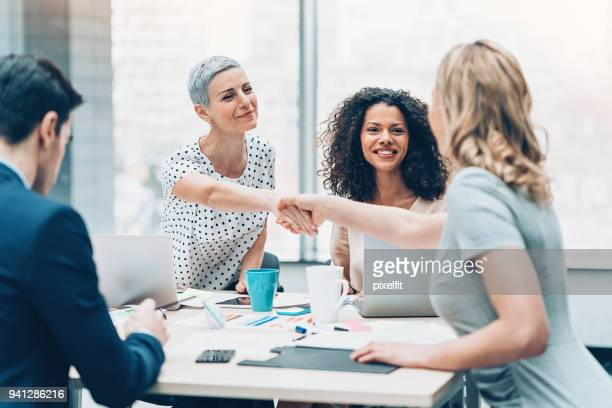 businesswomen shaking hands over the table - mergers and acquisitions stock pictures, royalty-free photos & images
