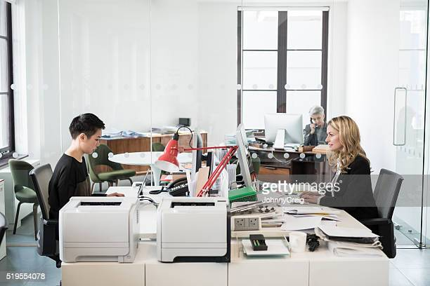Businesswomen sitting at desk in modern office using computers