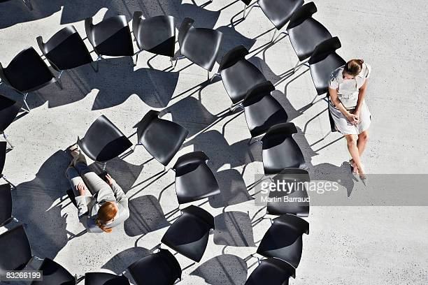 Businesswomen sitting in spiral of office chairs