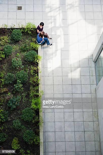 Businesswomen sitting on a planter