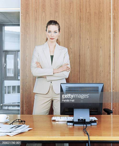 businesswomen standing behind desk, arms folded, portrait - beige suit stock pictures, royalty-free photos & images
