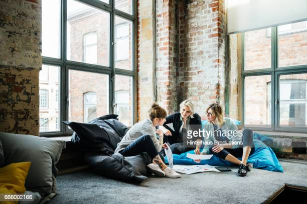 businesswomen talking during an informal meeting - oreiller geant photos et images de collection