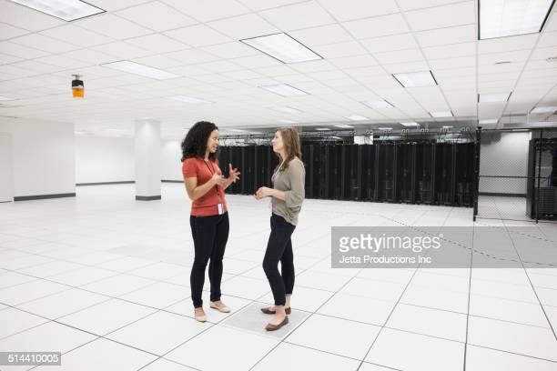 Businesswomen talking in server room