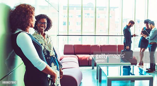 businesswomen talking in the office building lobby - clique stock photos and pictures