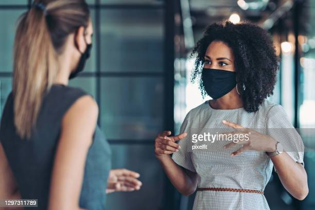 businesswomen talking in the office during the covid-19 pandemic - leadership stock pictures, royalty-free photos & images