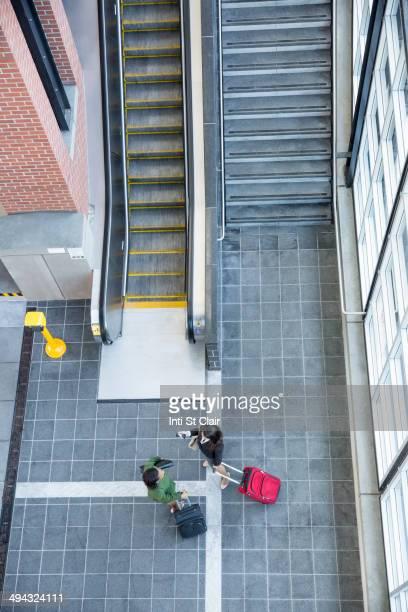 Businesswomen talking near stairs and escalator