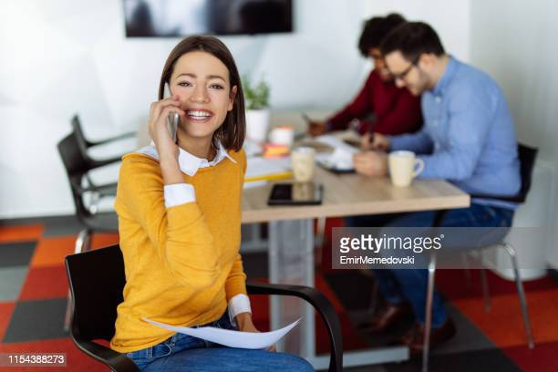 Businesswomen talking on phone while going through some paperwork