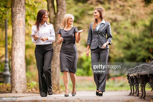 Businesswomen talking to each other while walking outdoors.