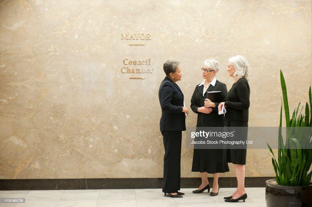 Businesswomen talking together in office corridor : Foto de stock