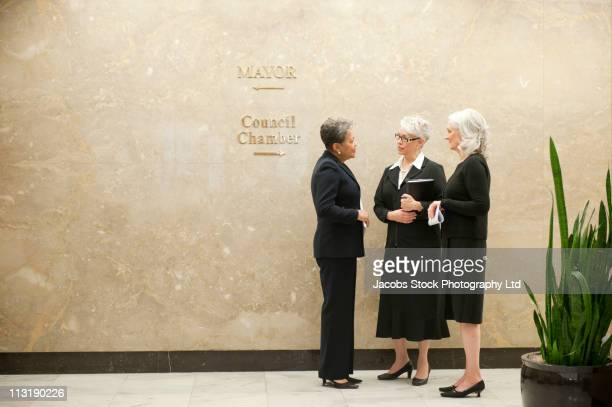 businesswomen talking together in office corridor - local politics stock pictures, royalty-free photos & images