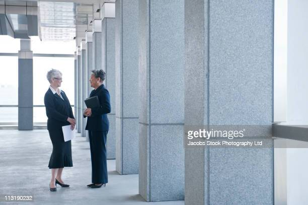 Businesswomen talking together in office lobby