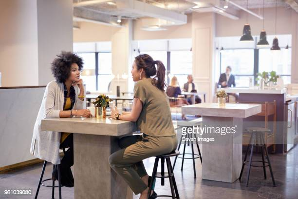 businesswomen talking while sitting in cafeteria at creative office with colleagues in background - coffee break stock pictures, royalty-free photos & images