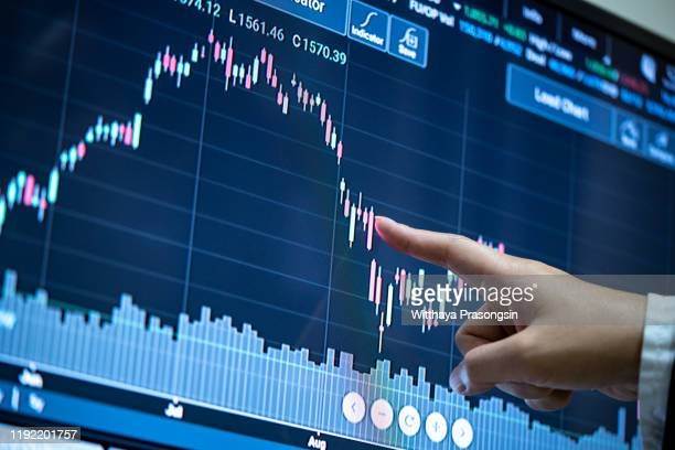 businesswomen touching stock market graph on a virtual screen display. - nasdaq stock pictures, royalty-free photos & images