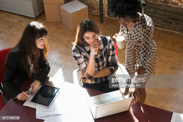 Businesswomen using digital tablet and laptop in office