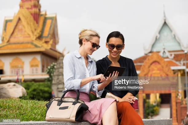 Businesswomen using digital tablet near temple, Phnom Penh, Cambodia