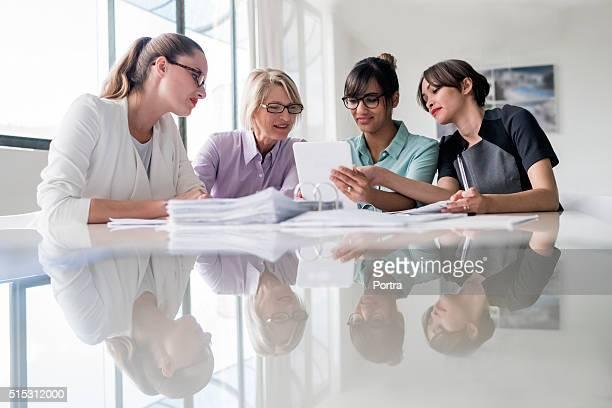 Businesswomen using digital tablet together at desk